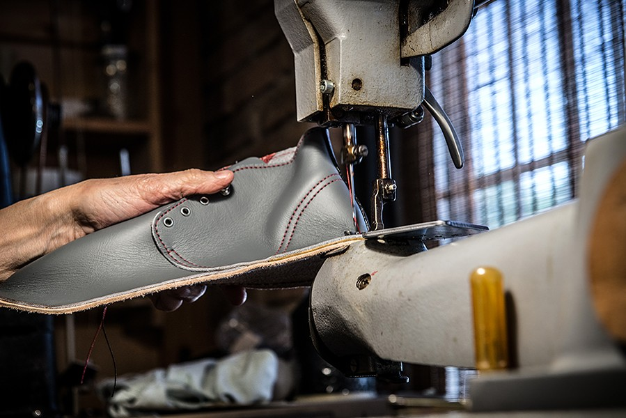 McIntosh helps students learn to sew the uppers to the midsole. - JAMIE RAMSAY