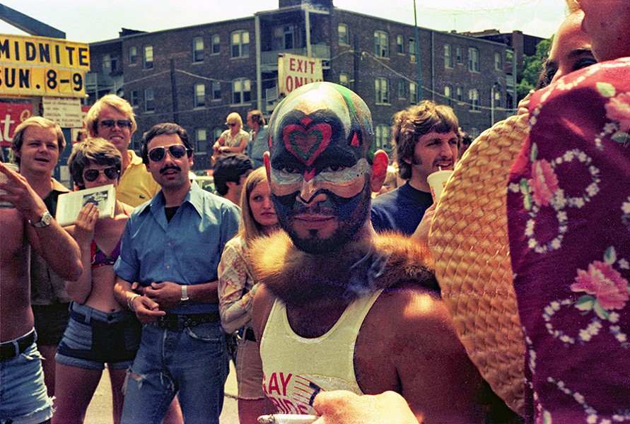 Psychedelic face paint, fur boa, and commemorative tank top announce the parade. - DIANE ALEXANDER WHITE