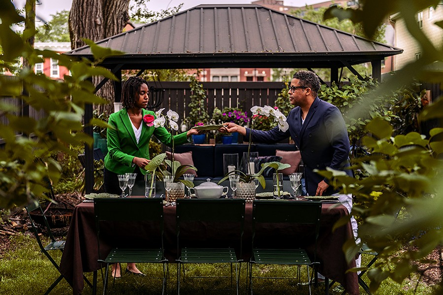 Mya Welch-Taylor, 13, and her father Raub Welch set a table for guests in their Bronzeville garden. - RYAN EDMUND