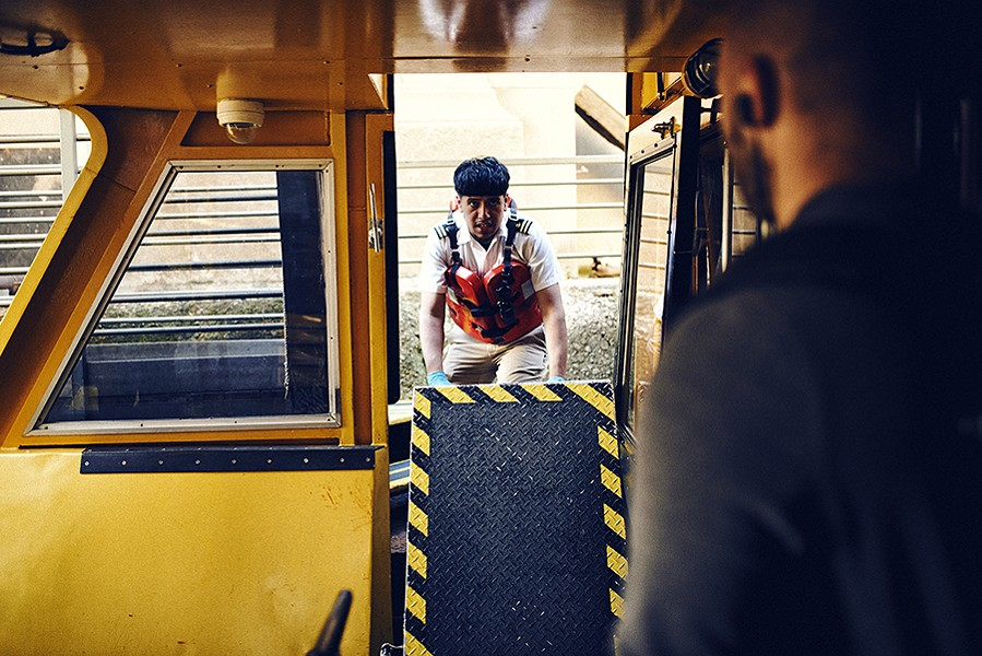 Deckhand Nick Leon installs a nonslip ramp for passengers to enter and exit the ship. - MAX THOMSEN