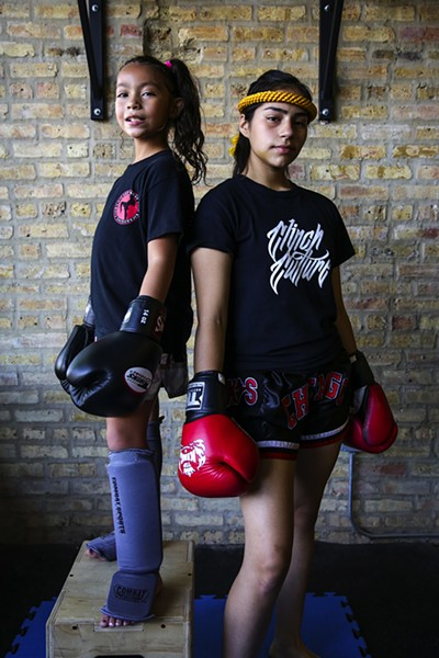 "Chanelle Ortiz, nine, and Paulina Lopez, 15, Portage Park Muay Thai  - Chanelle—""I like Muay Thai because the punches and kicks are fun. I first started with boxing, but I was getting bored of boxing, so my dad took me here to learn some kicks. I think the kids at school should try Muay Thai because it's fun, and my coaches are really nice."" - Paulina—""It really means a lot to coach someone like Chanelle. She started at a younger age than me, and I'm sure she can go so much further. And she's so good now, too! It's fun to have someone who looks up to me and that does [Muay Thai] with me. It's like a team, me and her, our team against this guys' world."" - GEOFF STELLFOX"