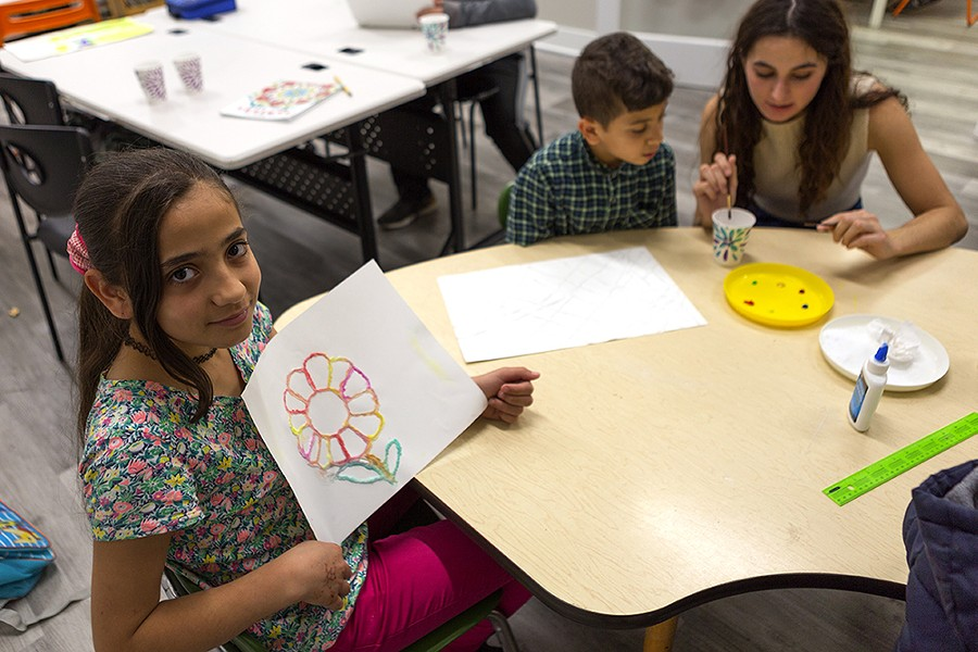 Fatima, 10, presents a flower she drew using salt and watercolors. In the background, her brother Sami learns from Ms. Amanda. The siblings moved to Chicago with their family about three years ago. - FARAH SALEM FOR CHICAGO READER