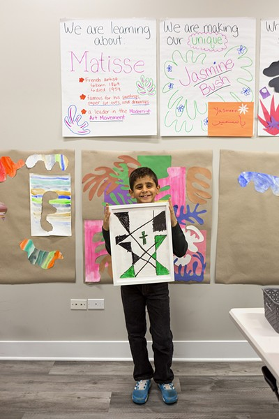 Hamza, 7, holds up a drawing he previously created at the afterschool program. Hamza moved to Chicago from Syria with his family about three years ago. - FARAH SALEM FOR CHICAGO READER