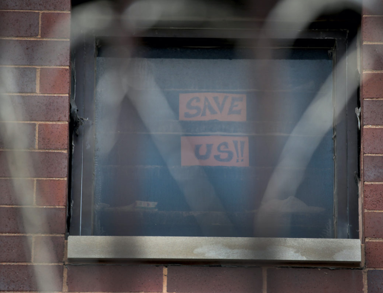 A sign pleading for help hangs in a window at the Cook County Jail complex on April 9, 2020, in Chicago, Illinois. - GETTY IMAGES