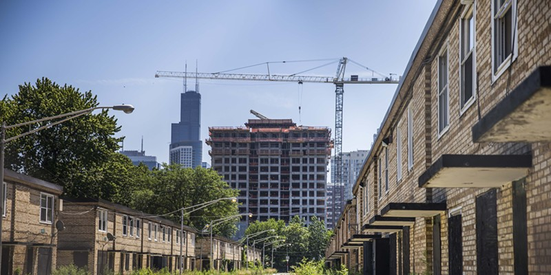 The remaining rowhouses of the Cabrini-Green public housing development stand empty as a new upscale apartment building is erected nearby.