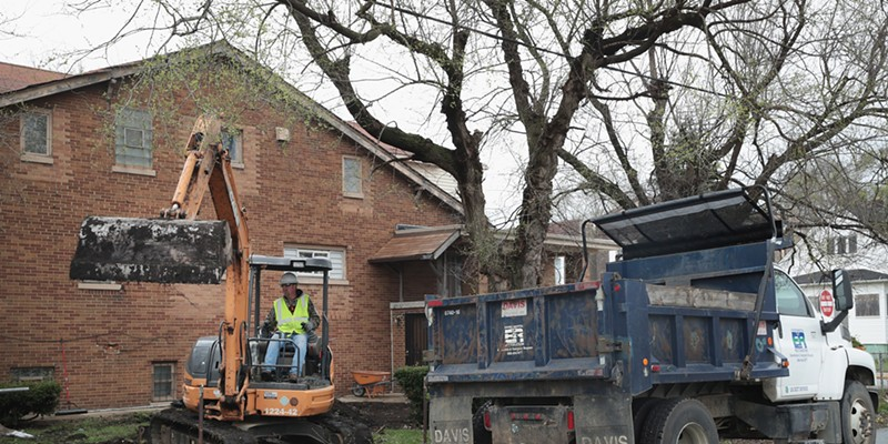 Workers remove lead-tainted topsoil from the yard of an East Chicago home near where U.S. EPA administrator Scott Pruitt met with area residents and community leaders Wednesday.
