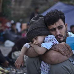 A father and child, Syrian refugees, waiting to board a bus on the northeastern Greek island of Lesbos.