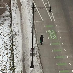 A pedestrian walks in the street to avoid a snowy sidewalk at Harrison and Wacker.