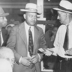 In this 1944 photo, A.T Walden (center), then-president of the Atlanta chapter of the NAACP, listens silently as an election official returns his ballot and explains he cannot vote in Georgia's democratic primary.