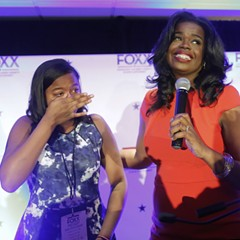 Kim Foxx, right, smiles at the crowd as her daughter, Kai, wipes tears from her eyes.