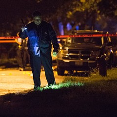 An evidence technician with the Chicago Police Department investigates the scene of a homicide in July.