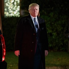 President-elect Donald Trump looks toward reporters as he arrives for a party at the home of Robert Mercer, one of his biggest campaign donors, Saturday.