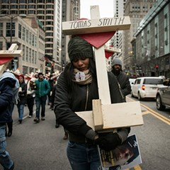 Latekia Sims and hundreds of other marchers carried wooden crosses for victims of gun violence during a peace march down the Magnificent Mile December 31.