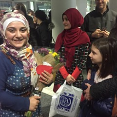 Baraa, left, a Syrian refugee, was greeted at O'Hare Tuesday night by her family and American sponsors.