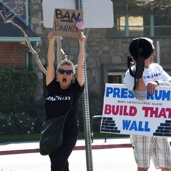 A protester, left, and a counterprotester hold signs at a demonstration against Breitbart News March 12 in Los Angeles.