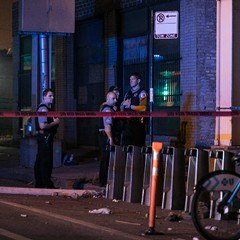 Chicago Police officers investigating the site of a fatal shooting in July