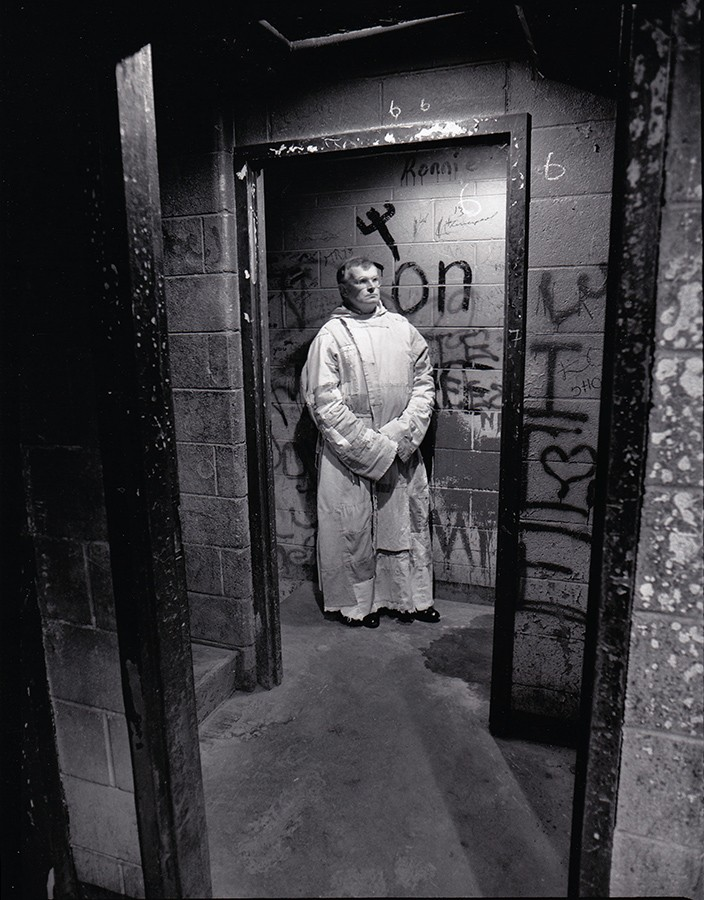 """By Lloyd Degrane - Degrane says: """"Brother Bill in a stairway at the Henry Horner Housing projects on the west side of Chicago. Brother Bill walked between warring gang members while they were shooting at one another. There were no lights on the stairwells—we walked in the dark, we climbed to the fifth floor. Finally one light dangled from above, I asked Brother Bill to stop. He did. I took the photo. Out of nowhere several gang members showed up and demanded to know what I was doing on their floor, then they saw Bill and it was all smiles and friendly acknowledgements. Bill turned to me and said 'Believe in Jesus.' I said, 'I believe in you Brother Bill.'"""