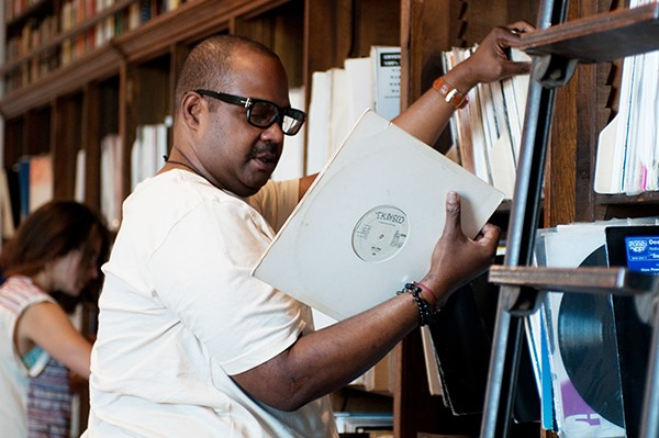 """Frederick Dunson, executive director of the Frankie Knuckles Foundation, checks out a 1979 promotional copy of the Ish single """"Don't Stop"""" from his old friend's collection. - ANDREA BAUER"""