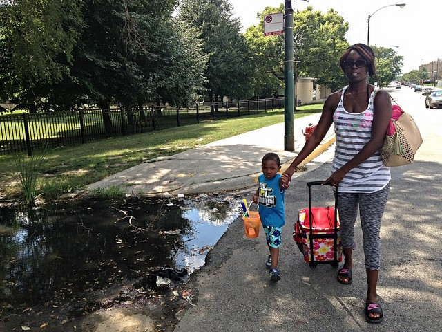 Caretha Carrol and her son Javaughn detour around a wide mud puddle on the way to 31st Street Beach. - JOHN GREENFIELD