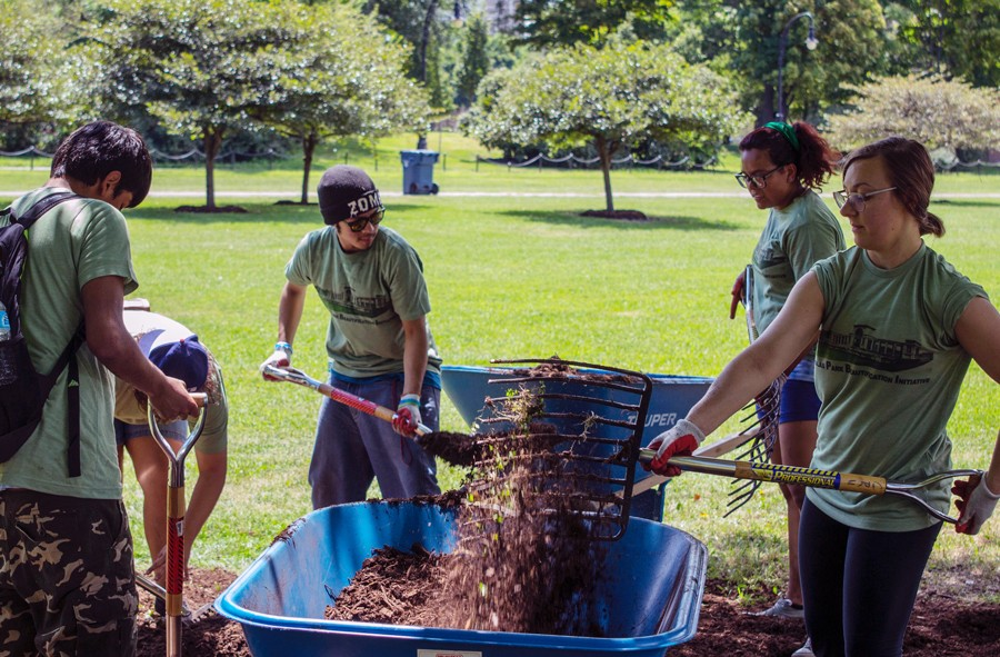 Volunteers spread mulch at a Douglas Park beautification event in August. - COURTESY RIOT FEST
