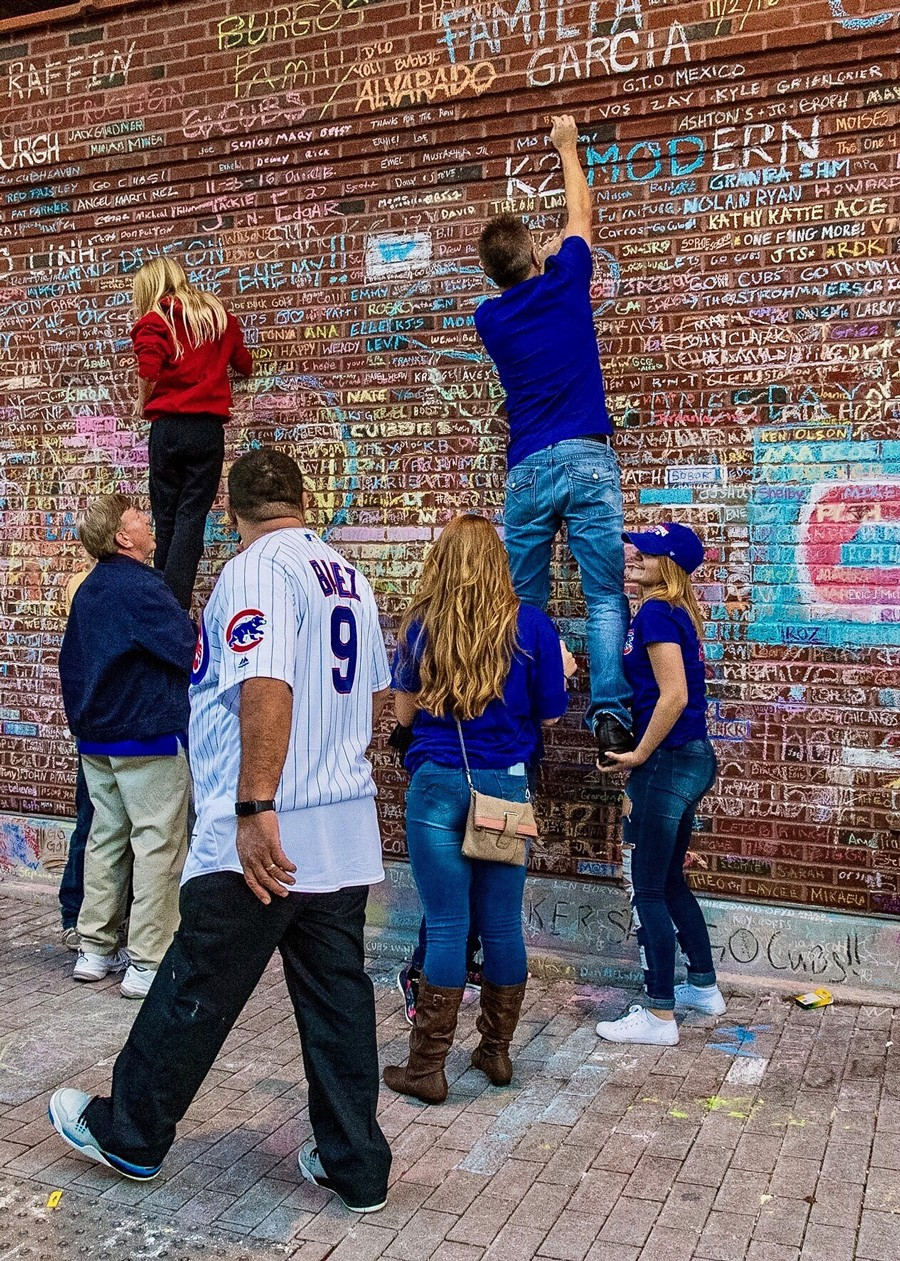 Large crowds of Cubs fans left heartfelt messages in chalk on Wrigley Field's exterior brick walls after the Cubs' historic World Series win. - PAUL BOUCHER
