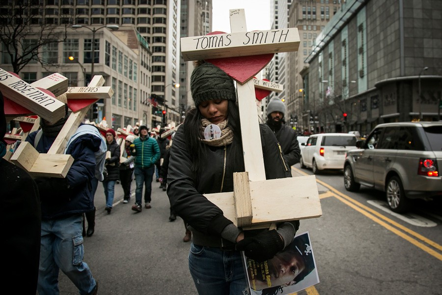 Latekia Sims and hundreds of other marchers carried wooden crosses for victims of gun violence during a peace march down the Magnificent Mile December 31. - ASHLEE REZIN/SUN-TIMES MEDIA