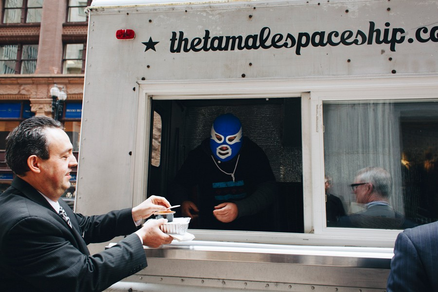 Lucha libre enthusiast Pepe Balanzar serves a customer of his Tamale Spaceship food truck. - DANIELLE A. SCRUGGS
