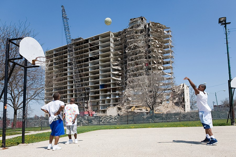 Teenagers play basketball while a Stateway Gardens building is demolished in 2007. - DAVID SCHALLIOL