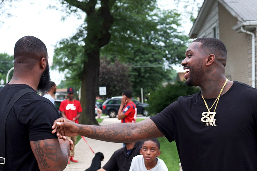 Phor (right) and his brother Don reminisce with friends on the block. - MORGAN ELISE JOHNSON