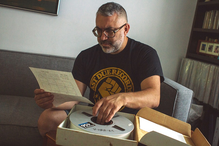 Jerome Derradji of Still Music inspects a multitrack tape from Record Al's house-music cache in his Humboldt Park home. For the photo shoot, he made the obviously unpremeditated choice to wear a T-shirt for another one of his labels. - KRIS LORI