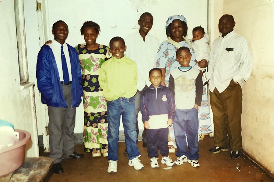 Bugumba with his parents and his six siblings in 2004, in the family's first apartment in Johannesburg, South Africa. His mother and father are at upper right, and Bugumba stands in front of his mother, in a white shirt with black sleeves. - COURTESY OF EPHRAIM BUGUMBA