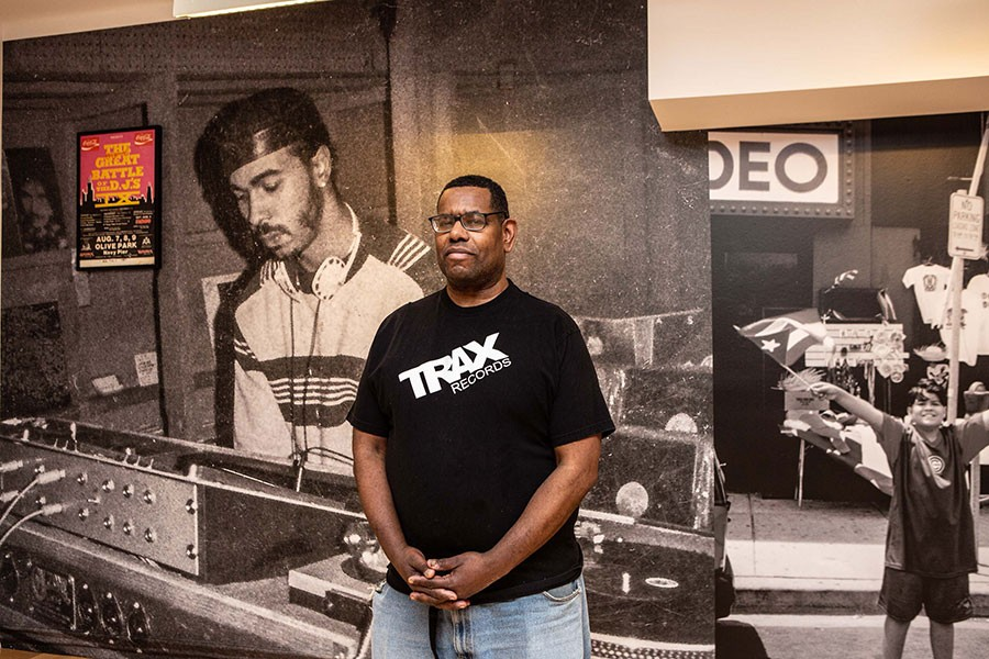 "Marcus ""Mixx"" Shannon at the Cultural Center, in front of a photo of house pioneer Ron Hardy at the Muzic Box - ALEXUS MCLANE"