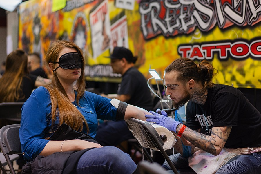 """Brooke Duhem, 26, from Elmwood Park, gets a tattoo from Curtis Cameron, an artist based in New Jersey. """"I basically just told him what my ideas were and I showed him a few different pictures,"""" Duhem says. """"I put the blindfold on, and from there I haven't seen it. Do you like it?"""" - PAT NABONG"""