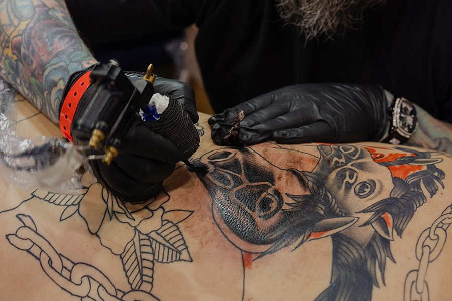 """Eric Smolinski, 41, from Lowell, Indiana, tattoos horses on Patrick Lopez's back. It """"doesn't have to stand for anything,"""" Smolinski says. It """"doesn't have to mean anything. It's just bold and out there and looks dope."""" - PAT NABONG"""