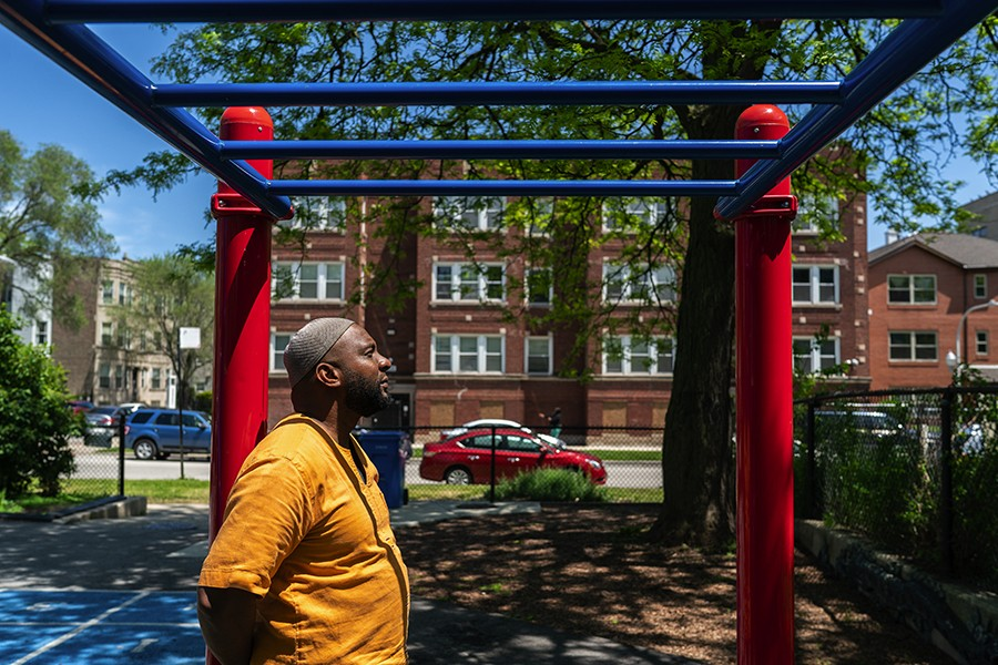 """Aaron """"Haroon"""" Garel stands at Huckleberry Park where they used to be a basketball court he says was a frequent gathering point for the Woodlawn community. He lived in the apartment building across the street for several years. - MAX HERMAN"""