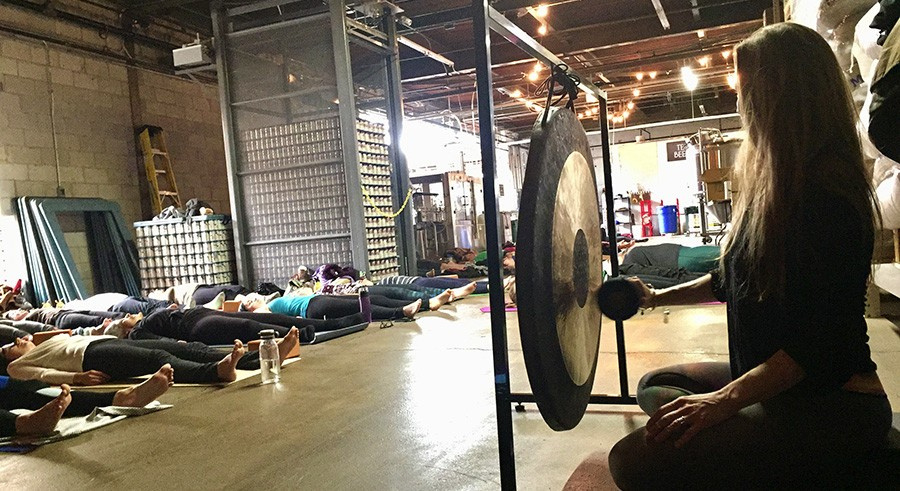 Jenny Arrington plays the gong while practitioners are in savasana at Temperance Beer Co. - COURTESY OF TEMPERANCE BEER CO.