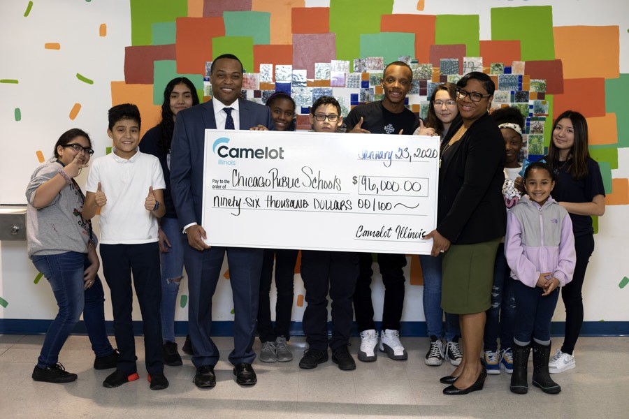 Camelot Illinois Acting General Manager, Keith Horton, presents $96,000 check to fund CPS computer science initiatives at Dyett High School and Walsh Elementary to principal, Patricia J Harper Reynolds and students.