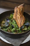 The green chile fish stew has perfectly cooked mussels, clams, and hake chunks, and is mounted atop a leather trivet.