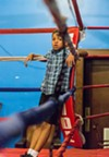 Between sparring matches, kids take to the ring, throwing themselves against the ropes or lounging on the posts.