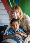 Founder Sally Hazelgrove, 54, with Javion Copeland, 10. Hazelgrove acts as a second mom to many of the members, talking to them about their days, making sure they stay out of trouble, and telling them she loves them.