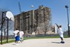 Teenagers play basketball while a Stateway Gardens building is demolished in 2007.