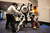 A pair of fellow cosplayers help Brian Beech (center) prepar his costume, Atlas from the video game <em>Portal 2</em>, for the Crown Championships of Cosplay during C2E2 2014.