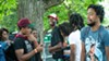 Saba hangs with friends and family before his set. He's in the red and white hat, Frsh Waters has on a maroon hat, and Joseph Chilliams wears a Rock T-shirt.
