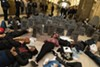 "CPS high school students and supporters of #NoCopAcademy hold a ""die-in"" at City Hall in March 2017. The cardboard tombstones bear the names of people who've been killed by Chicago police and those of the schools and mental health clinics closed by Mayor Rahm Emanuel during his first term."