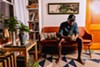 Damiane Nickles studies a small aloe plant in his living room.