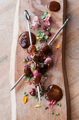 A skewer of duck hearts is slathered in a lavender barbecue sauce. - ANDREA BAUER