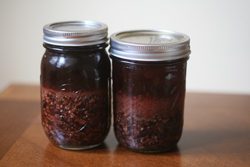 Vodka (left) and rum infused with cacao nibs, just before straining