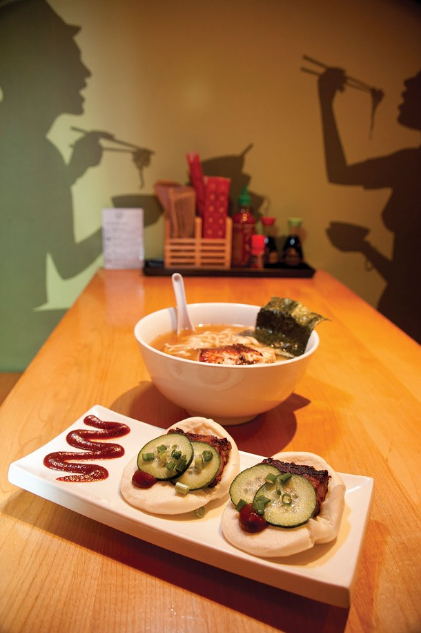 A bowl of udon, miso broth, and salmon; a platter of steamed pork buns at Yum Yum Noodle Bar. - ROY GUMPEL