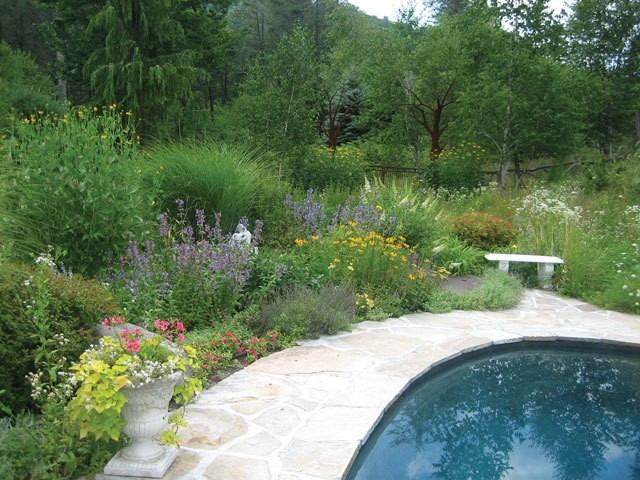 A garden built and maintained by Carol Washington's serenity gardens blending shrubs, perennials, grasses, bulbs, and annuals.