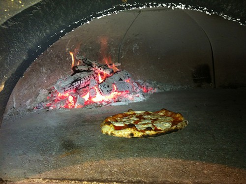 A Margherita pie cooking in the wood-fired oven